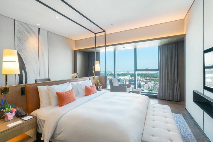 Lit XXL et grande baie vitrée dans la chambre avec un style plus discret